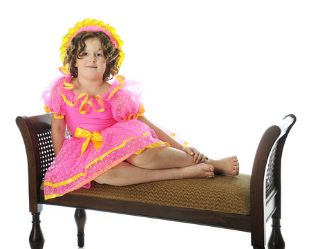 An elementary Shirley Temple impersonnater happily sitting mermaid-style on a padded bench. On a white background. photo