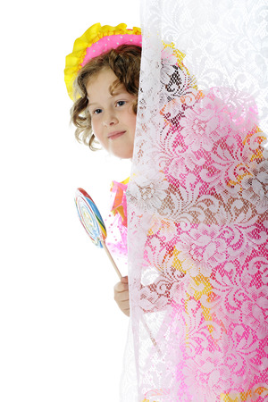 An elementary actress peeking from behind a lace curtain with a giant lollipop as she's prepared to play Shirley Temple.  On a white background. photo