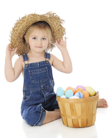 farm girl: An adorable preschool farm girl happily sitting in her ragged straw hat with a fruit basket full of Easter eggs beside her.  On a white background.