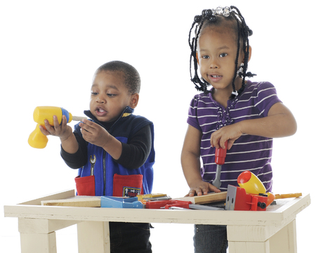 A toddler brother and preschool sister plalying together with the toy tools on a workbench.  Taken on a white background.
