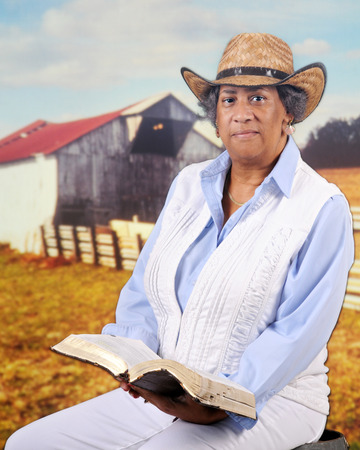 sittting: A mature African American cowgirl sittting on on old barrel with her opened Bible  before a fenced pasture and old barn.