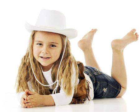 Een blootsvoets cowgirl gelukkig ontspannen op haar buik. Op een witte achtergrond. Stockfoto