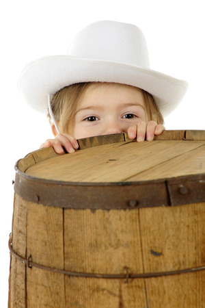 An adorable preschool cowgirl peeking over the top of a rustic old barrel.  On a white background. photo