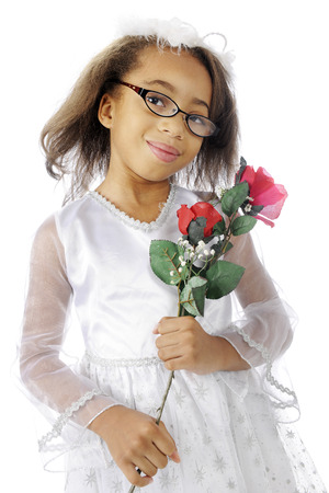 dressed up: A pretty, dressed up, black elementary girl happily carrying red roses.  On a white background.