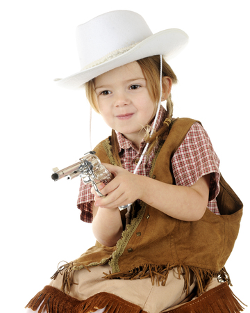 Closeup of a beautiful little preschool cowgirl happily shooting her capgun with two hands.  On a white background. photo
