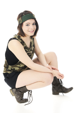 girl squatting: A beautiful girl looking at the viewer while squatting in her camouflage headband and sleeveless shirt.  Shes also in shorts and combat boots.  On a white background.