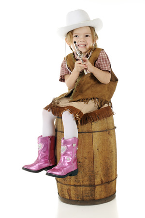An adorable preschool cowgirl happily showing her cap gun while sitting on a runstic barrel.  On a white background.