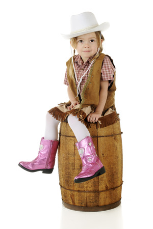 An adorable preschool cowgirl sitting on a rustic wood barrel.  On a white background.