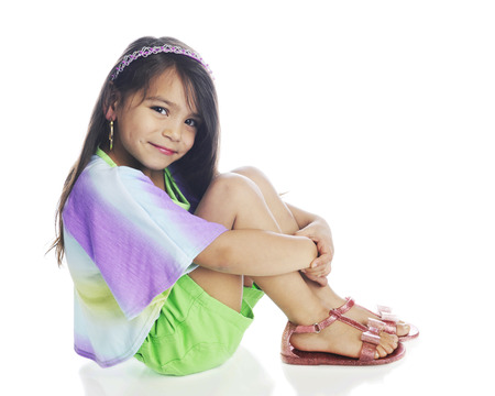looking at viewer: A beautiful young girl happily looking at the viewer while sitting pretty in her shorts, multicolored shirt and sandals.  On a white background.