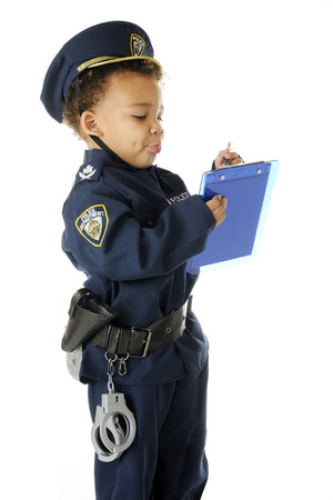 traffic cop: An adorable preschool traffic cop in full uniform, writing a ticket.  On a white background. Stock Photo