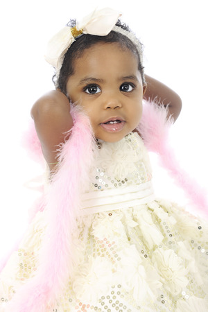 dressed up: Portrait of a beautiful baby girl all dressed up in a white hair bow, sequin dress and pink boa.  On a white background.