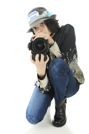 girl squatting: An attractive young teen school photographer squatting to shoot from a low position.  On a white background.