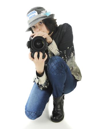 en cuclillas: Una atractiva joven escolar adolescente fotógrafo cuclillas para disparar desde una posición baja. Sobre un fondo blanco.