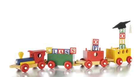 hauling: A colorful toy train hauling alphabet blocks arranged to spell out Class of 2016, a graduation cap on the last blocks.  On a white background.