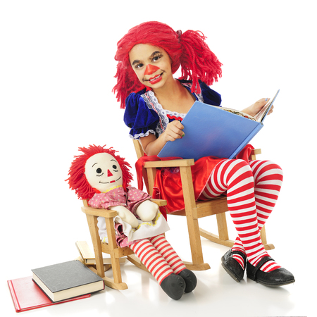 rag doll: A young living rag doll in a rocking chair happily reading to her own rag doll, also in a rocking chair.  On a white background.