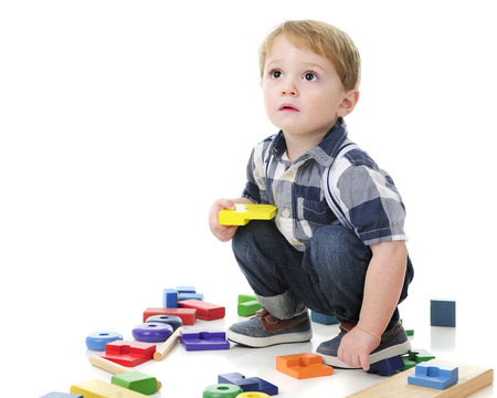 squatting: An adorable toddler boy looking up and squatting as hes surrounded by wooden blocks and a stack toy.  On a white background.