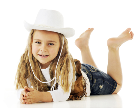 denim shorts: A barefoot cowgirl  happily relaxed on her belly.  On a white background. Stock Photo
