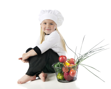basketful: An adorable preschooler in her chefs outfit, sitting by a wire basketful of vegetables.  On a white background.