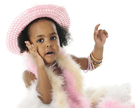 2 year old: Close-up image of an adorable 2 year old diva in beads, boas and bangles.  Shes looking at the viewer with one hand on her cheek.  On a white background.