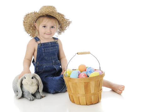 cute young farm girl: An adorable preschool far girl petting a bunny next to a fruit basket full of colorful eggs.  On a white background.