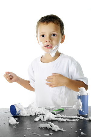attempts: An adorable preschooler looking worried in the midst of the shaving cream mess hes made as he attempts to shave like his dad.  On a white background.