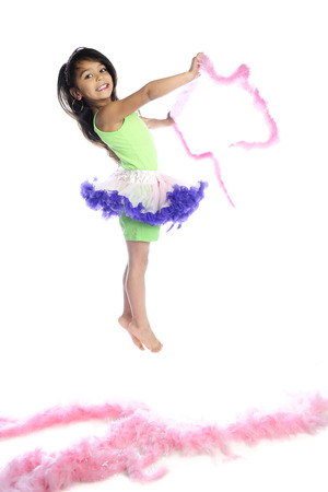 boas: A beautiful young girl jumping for joy in her tutu and with pink boas.  On a white background.