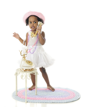french fancy: An adorable girly girl stading in her petticoat, pearls and hat while talking on a fancy French phone.  On a white background. Stock Photo