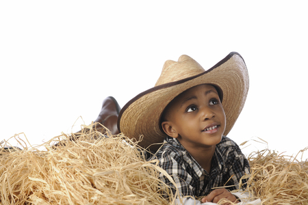 oversized: An African cowboy happily resting in the hay cowboy boots and an oversized hat.  On a white background.