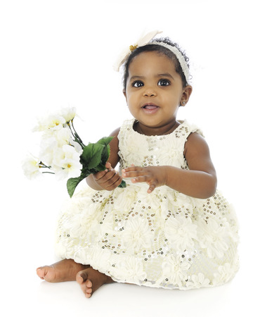 hair bow: A beautiful, barefoot baby girl in a white hair bow and sequin dress.  Shes happily holding a small bouquet of white flowers.  On a white background.