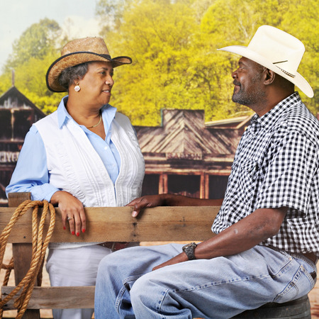 western town: A mature, senior African American couple flirting over a fence in an old western town. Stock Photo