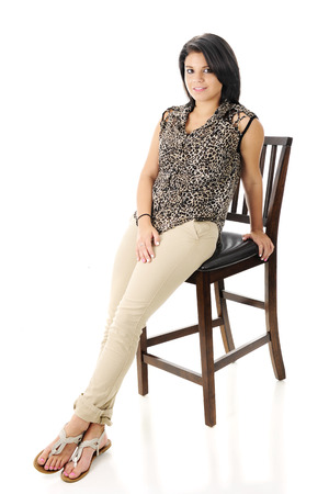 sandles: A beautiful teen girl happily leaning on a tall wooden chair.  On a white background. Stock Photo