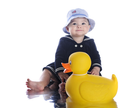 rubber ducky: An adorable baby sailor girl sitting with her giant rubber ducky