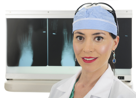 scrub cap: Close-up of a  beautiful female surgeon standing before her lightbox displaying foot x-rays.  On a white background. Stock Photo