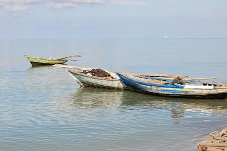 Drie vissersboten met peddels en vistuig dat verankerd is in het Caribisch gebied.