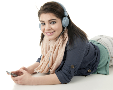 looking at viewer: A beautiful teen girl looking at the viewer while wearing headphones and listening to her cell phone.  On a white background.