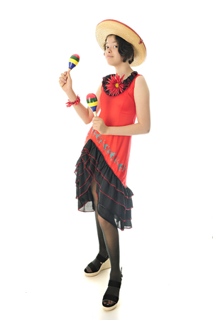 looking at viewer: A pretty young teen dressed for celebrating Cinco de Mayo, looking at the viewer while shaking maracas.  On a white background. Stock Photo