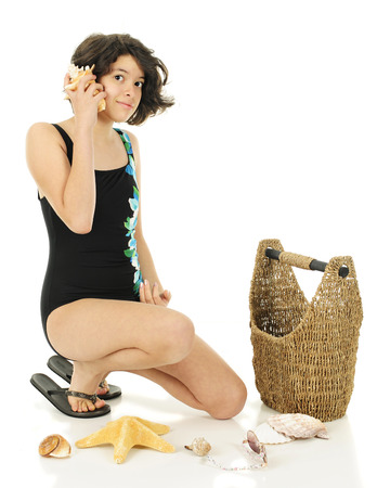 swim suit: An attractive young teen in her swim suit listening to a conch shell with her collections basket and other shells nearby.  On a white background.