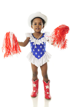 black cowgirl: An adorable African American happy in her western, star studded red, white and blue outfit gently shaking her pom-poms.  On a white background.