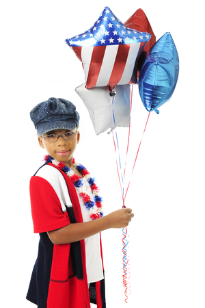 looking at viewer: A young elementary girl looking at the viewer as she holds a bunch of red, white and blue balloons.  On a white background.