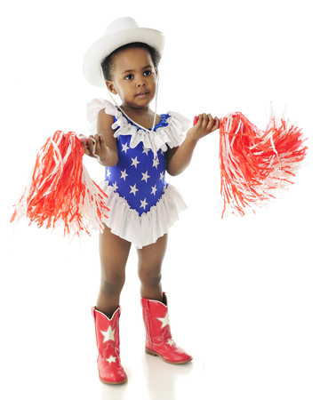 2 year old: An adorable 2 year old wigging her pom-poms while in her star studded,western red, white and blue outfit.  On a white background. Stock Photo