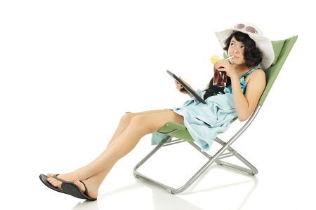 chilled out: A slim young teen chilling out on a beach chair in her beach outfit with her ipad and iced tea.  On a white background.