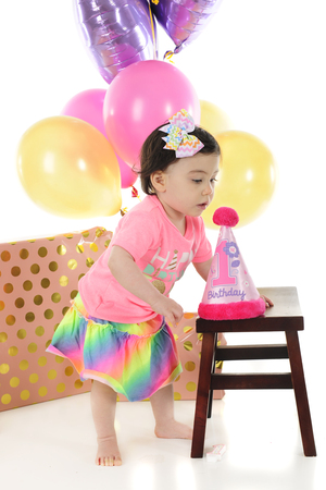 stool: An adorable baby girl studying the fluffy pink top on her birthday hat.  Wrapped gifts and multiple baloons are behind her.