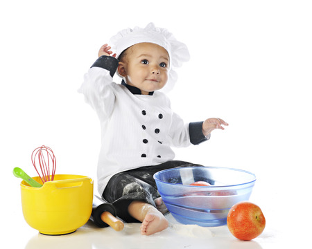 messed up: An adorable baby boy messed up with flour in his chefs outfit.  Bowls of apples and cooking utensiles are nearby.  On a white background. Stock Photo