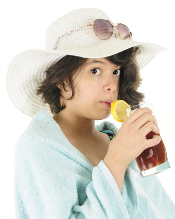towel beach: Close-up of a pretty young teen ready for the beach in her swim suit, towel, beach hat and sunglasses.  Shes looking at the viewer as she sips on her iced tea.  On a white background. Stock Photo