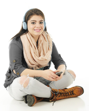 crosslegged: A pretty teen girl sitting cross-legged on the floor happily listening to her cell phone with headphones.  On a white background. Stock Photo