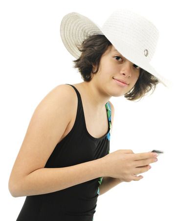 Closeup of an  attractive young teen holding her phone while wearing her bathing suit and a beach hat.  On a white background.