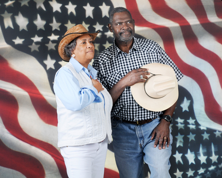 honoring: A mature African American cowboy couple honoring their country with hands over their hearts.  They stand proudly before the stars and stripes. Stock Photo