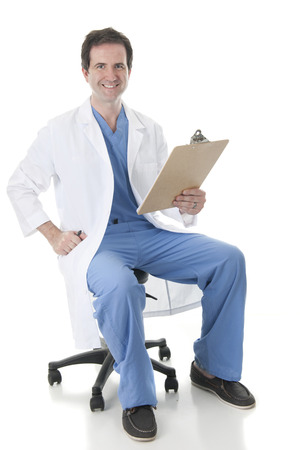 Full length image of a physician in scrubs and labcoat, looking at the viewer as he sits on his rolling stool with a clipboard in hand. On a white background.