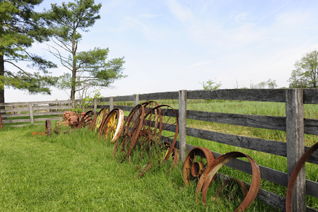 old wood farm wagon: Rusty wagon wheels leaning against a rustic rail fence thats surrounded by grassy fields.