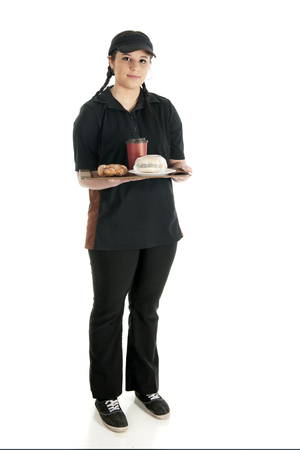 slacks: A pretty young waitress stanidn with full tray -- a wrapped breakfast sandwich, a twisty donut and a cup of coffee.  On a white background Stock Photo